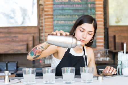 Female bartender pouring cocktail from shaker into glasses on bar counter
