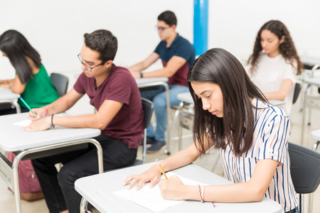 Group of teenage pupils taking test in classroom at university