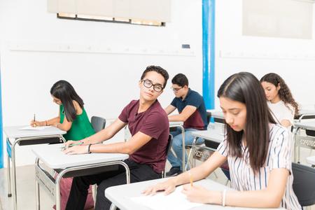 Hispanic boy cheating in admission exam at classroom