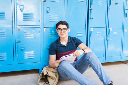 Portrait of a smiling male student reading a book in corridor before exam