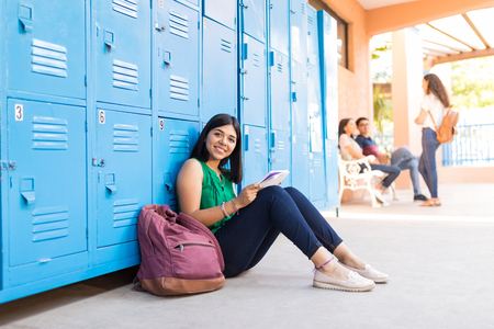 Portrait of attractive young girl studying while sitting by backpack in school corridor