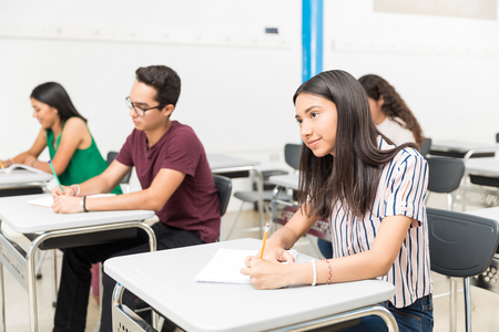 Teenage students writing in books while learning in classroom at high school