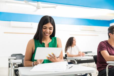 Smiling Hispanic girl using digital tablet while studying in high school Reklamní fotografie