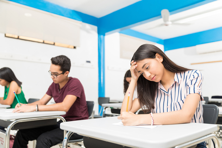 Group of teenage students taking a test in classroom at high school