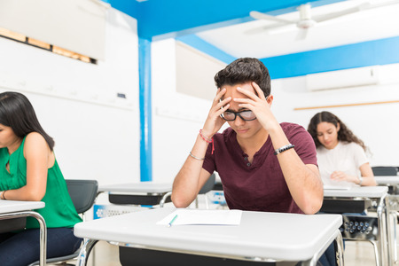 Teenage pupil worried in test while sitting with classmates in school