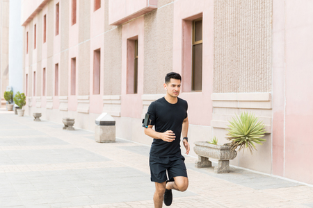 Male jogger running while listening music in city Stock Photo