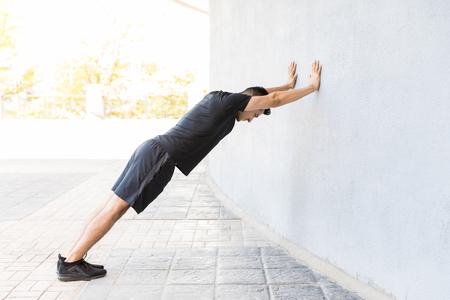 Profile shot of focused man in sportswear pushing wall on footpath in city