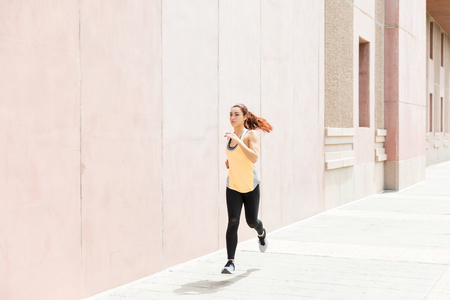 Full length of female jogger jogging on sidewalk by wall in city