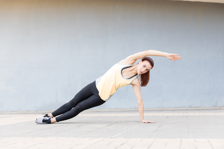 Charming fit runner making eye contact while balancing on one arm