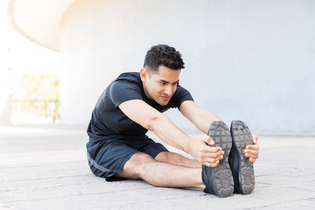 Fit handsome man warming up before running while sitting on footpath