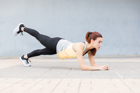 Full length of strong woman in plank position with leg up Reklamní fotografie