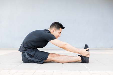 Motivated and concentrated young man stretching foot and doing morning exercise