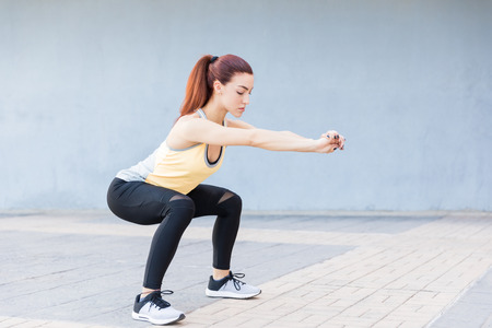 Beautiful woman performing squatting exercise while stretching hands on sidewalk Stock Photo - 124767273