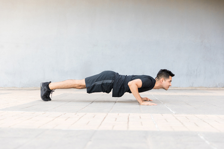 Side view of man warming up and doing push-ups as part of his training