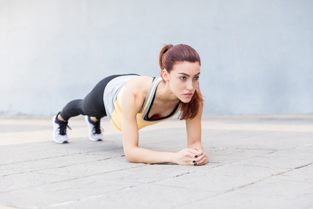Good looking young woman doing a plank exercise in city