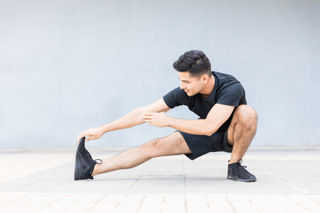 Full length male athlete stretching his muscles before a jog against wall
