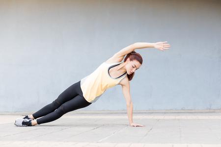 Caucasian young woman holding the side plank pose on sidewalk Reklamní fotografie