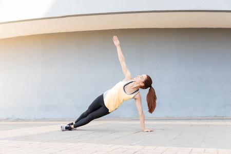 Active female athlete practicing side plank on sidewalk