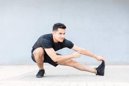 Full length of athletic man doing stretching exercise before his run