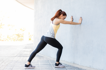 Full length side view of Caucasian woman pushing against wall Stock Photo - 124767285