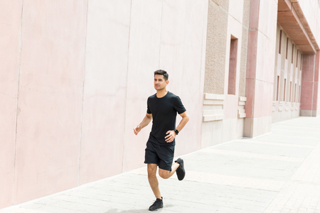 Full length of determined runner jogging in city Stock Photo - 124767286