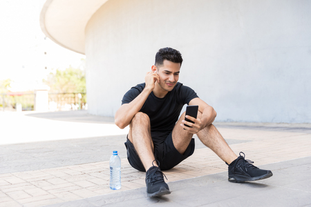 Handsome Latin man picking a good song and getting ready for his training