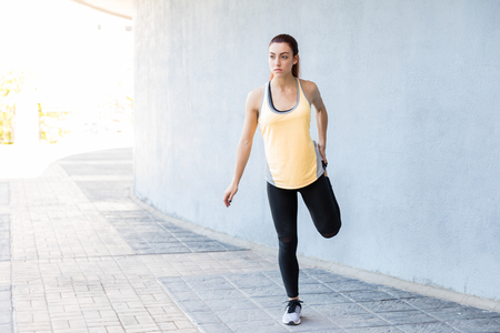 Female jogger stretching her leg before a long run while standing on sidewalk Stock Photo - 124767292