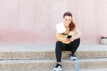 Smiling sporty woman using smartphone after exercise in city