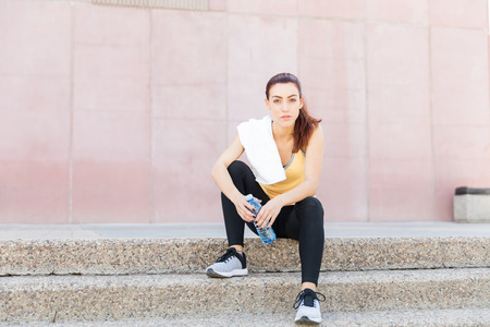 Full length portrait of gorgeous woman with water bottle sitting on steps after workout Stock Photo