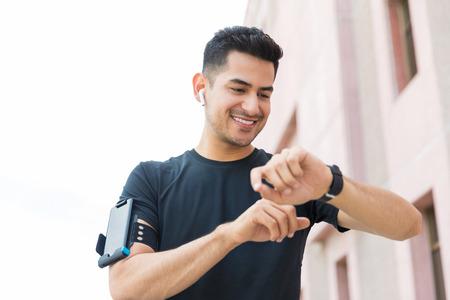 Handsome young man preparing smartwatch before running in city Reklamní fotografie