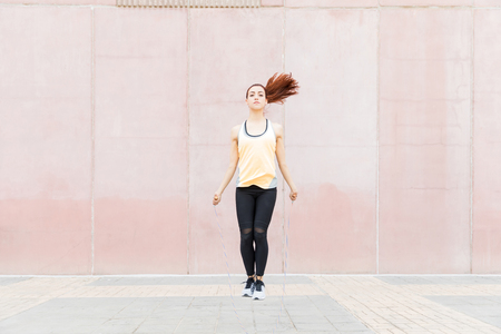 Full length of sporty female exercising with jumping rope during training