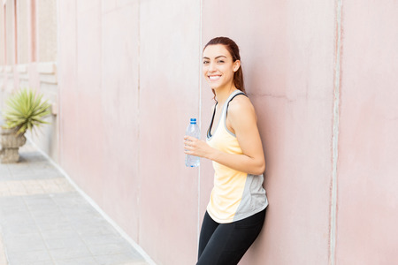 Smiling sporty woman refreshing after tiring workout in city