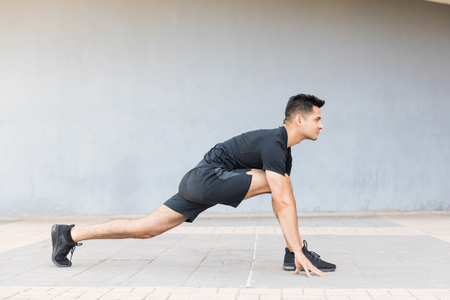 Handsome male athlete doing low lunge stretch on sidewalk