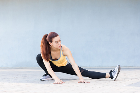 Flexible and sporty woman warming up with determination in city Stock Photo - 124767686