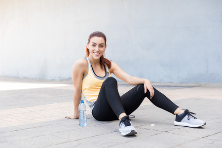 Full length of happy female athlete taking a water break after jogging in the city Stock Photo