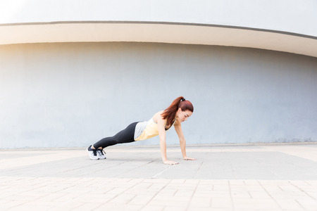 Full length of beautiful athlete exercising after jogging on footpath