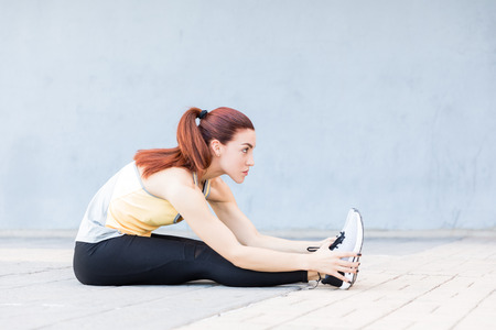 Side view of sporty woman bending while sitting on footpath in city Stock Photo - 124767713