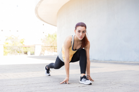 Portrait of attractive young woman doing low lunge pose on sidewalk Reklamní fotografie