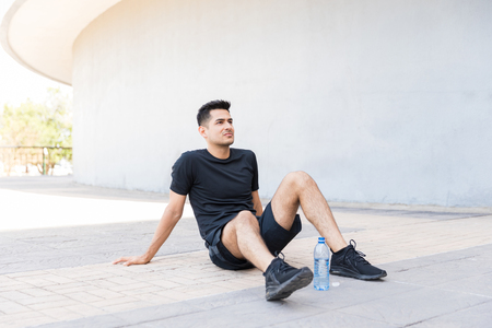 Thoughtful male athlete sitting by water bottle after exercise during summer Stock Photo