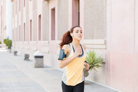 Confident female athlete doing fitness exercise while listening music in city