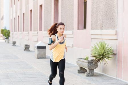 Determined Caucasian woman in sportswear jogging on sidewalk