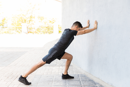 Determined young Latin man stretching calf while leaning on wall