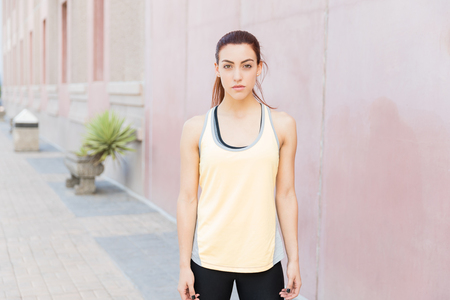 Confident female jogger in sportswear standing in city