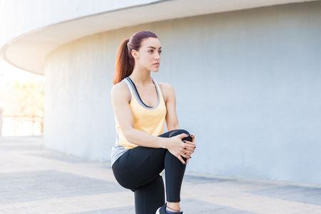 Determined woman looking away while doing stretching exercise on footpath