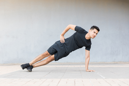 Full length of determined young athlete doing side plank exercise on sidewalk