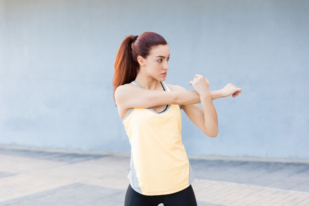 Focused woman in sports clothing stretching hand to stay fit