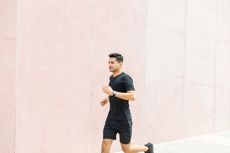 Dedicated male jogger running by wall in city