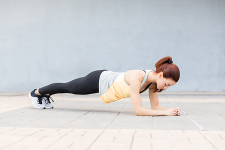 Pretty young woman doing a plank to strengthen her abs on footpath Reklamní fotografie