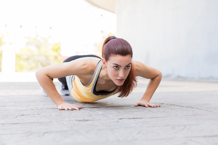 Determined Caucasian woman doing some push-ups before jogging