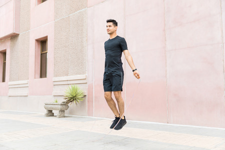 Confident male athlete exercising with jumping rope in city